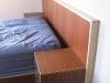Custom bed with wall-hanging headboard and floating shelf.