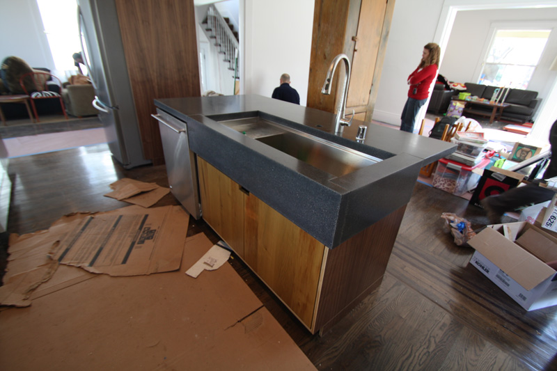Kitchen island with wrap-around dark grey concrete countertop.