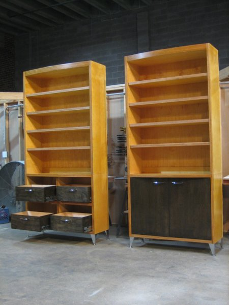 Two large bookshelves built from exposed-edge birch plywood shellacked different colors.