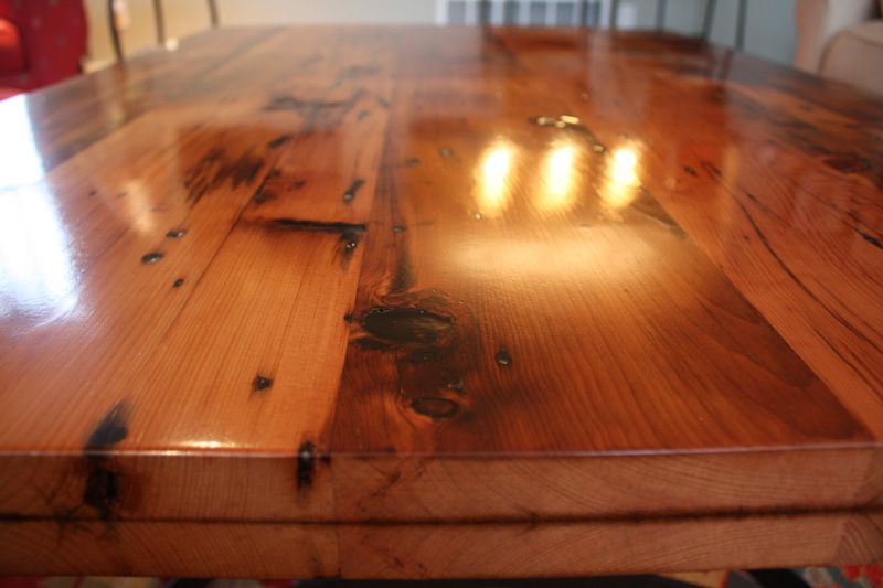 Coffee table top built from old pine sheathing removed from clients\' house during remodel. Nail holes and knots are filled with clear resin.