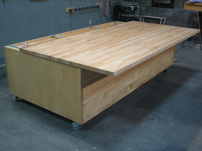 Large work table with sliding solid maple butcher block top and pull-out shelves.