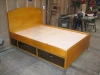 Bed built from birch plywood. Stained to match tall storage pieces in same space. Bed has four large drawers and two doors for storage.