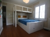 Bunk bed has a double mattress below with a transverse-mounted single above. Base has drawers and cabinets. Ladder and railings are solid ash.