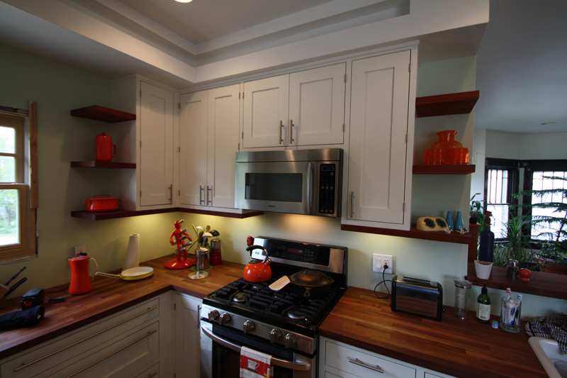 Kitchen cabinets with solid cherry butcher block countertops and floating shelves.