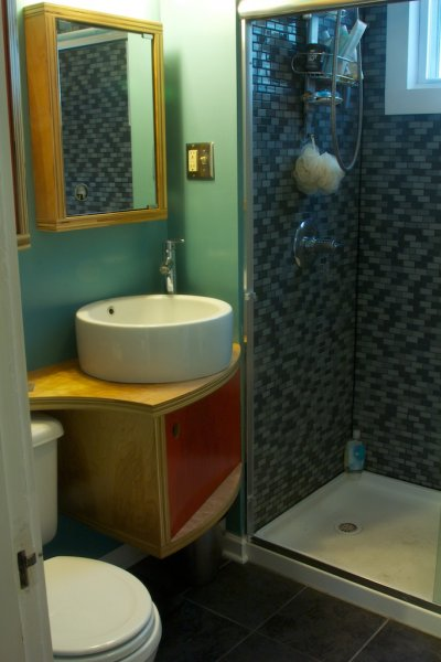 Kim\'s bathroom. Exposed-edge plywood vanity, shelves and medicine cabinet with bright red shellacked doors.